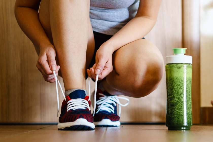 woman ties shoe next to smoothie