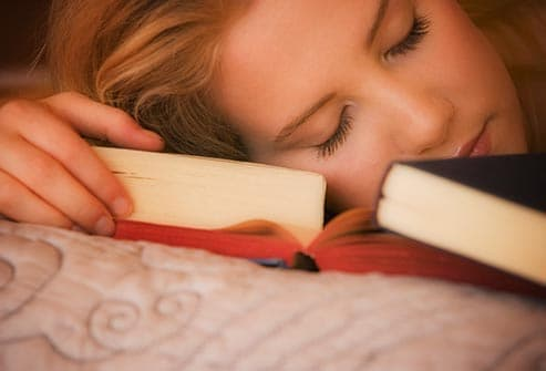 student sleeping with books