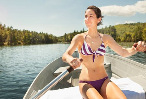 Woman in bikini rowing boat