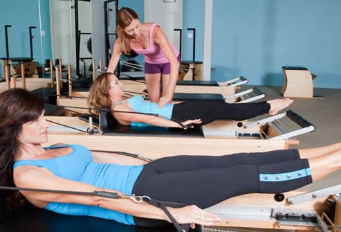 Women doing pilates with trainer