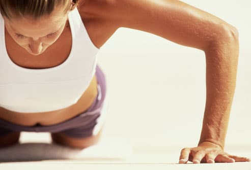 Woman doing pushup on knees