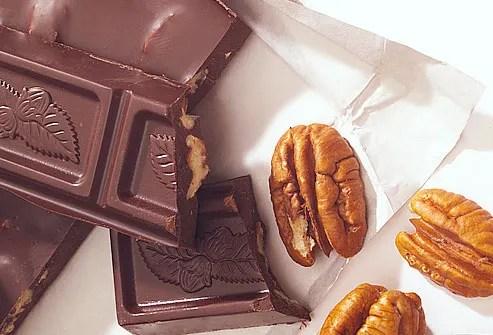 Bar of chocolate beside pecans