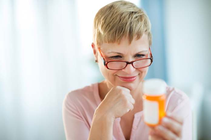 woman looking at medication bottle
