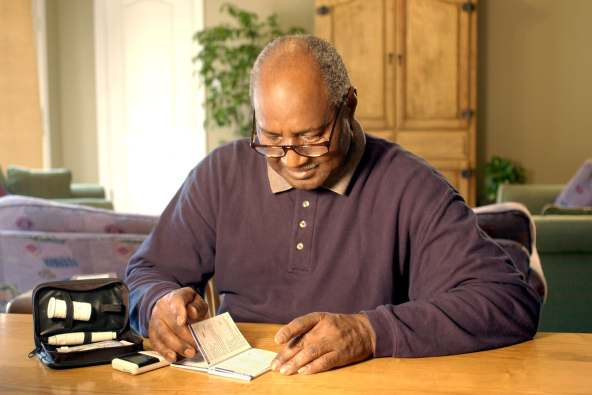 photo of man reading glucose level meter manual