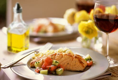 Grilled fish and veggies on white plate