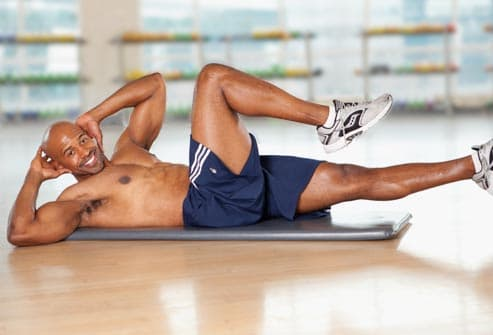 man doing bicycle exercise - The Best Flat-Abs Moves for Men