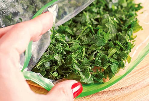 bag of greens on cutting board