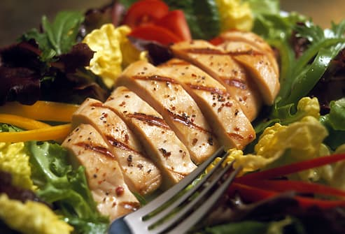 Sliced chicken breast on salad