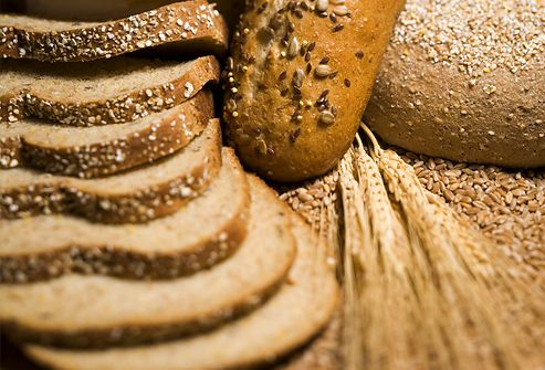 Close-up of wheat stem and slices of brown bread