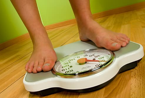 bare feet standing on a weight scale