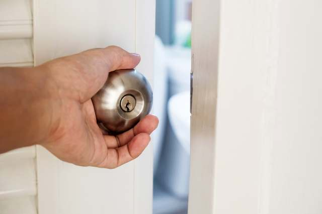 mans hand on bathroom door knob