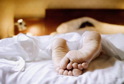 feet of person sleeping in bed