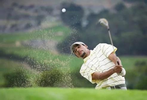 golfer hitting ball from sand bunker