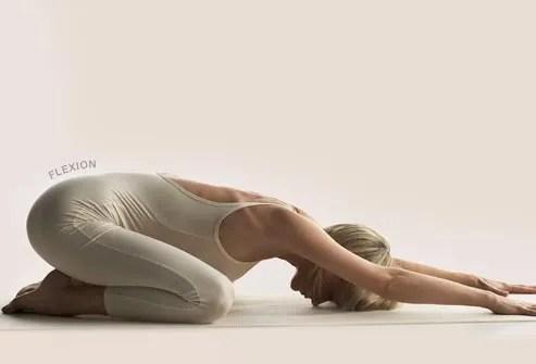 woman practicing yoga child pose