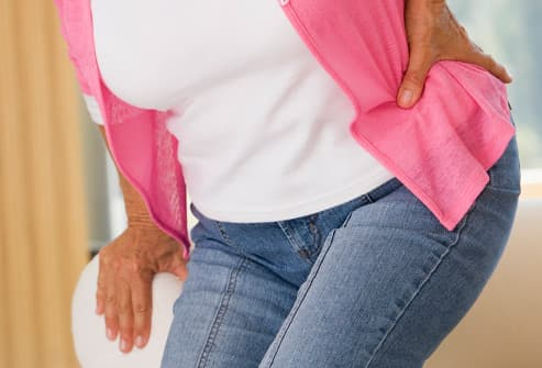 woman with back pain standing up