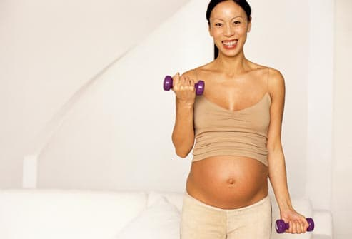 pregnant woman using hand weights