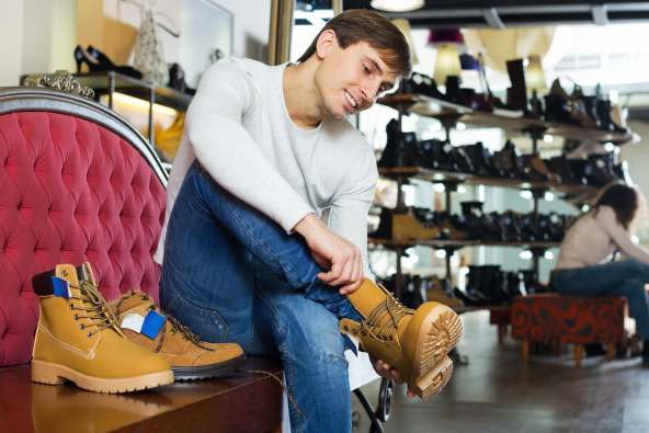photo of man trying on shoes