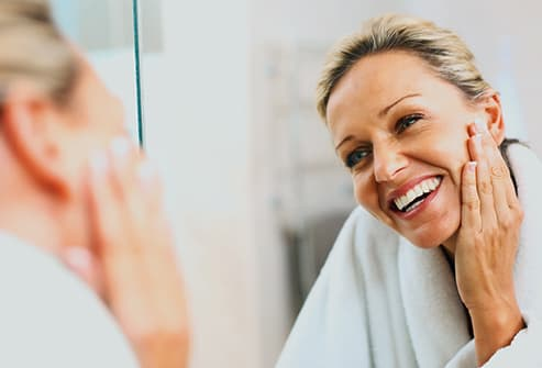woman looking at face in mirror