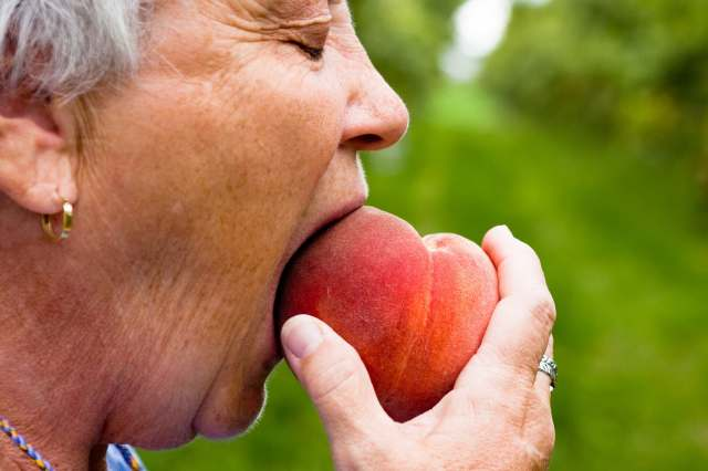 mature woman eating peach