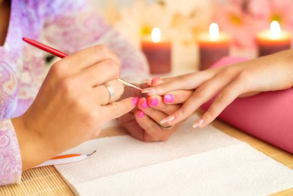 photo of woman having manicure done
