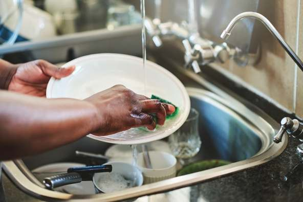 photo of woman washing dishes