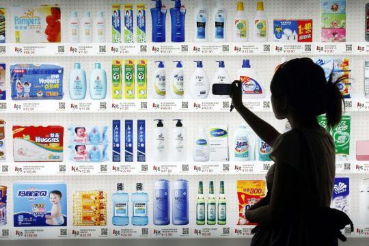 Eine Chinesin scannt QR-Codes von Kosmetik- und Pflegeprodukten in einem Supermarkt. Von der wachsenden Mittelschicht des Riesenreiches träumen westliche Konzerne als kaufkräftige Zielgruppe