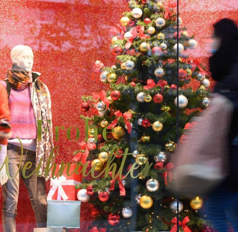 """December 8th, 2020, Saxony, Dresden: A passerby walks with a paper bag on the shopping street Prager Straße in front of a shop window with the inscription """"Merry Christmas"""" along.  As part of stricter protective measures against the spread of the corona pandemic, schools, daycare centers, after-school care centers and many shops in the Free State are to be closed from December 14, 2020.  Photo: Sebastian Kahnert / dpa-Zentralbild / dpa +++ dpa-Bildfunk +++"""