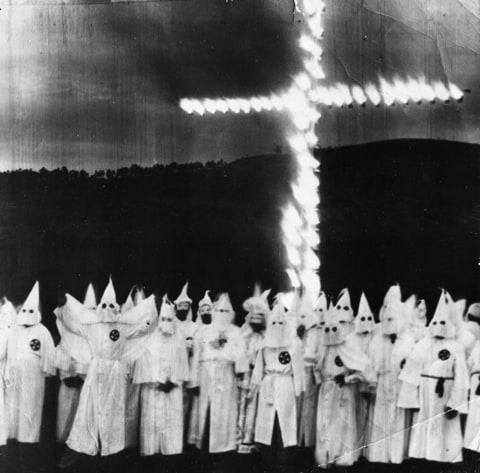 News photograph of a Ku Klux Klan members as they march in full costume, Atlanta, Georgia , circa 1955.