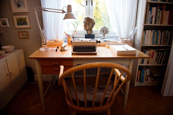 Kirjoituskone pöydällä. Pöydän takana ikkuna, jolla on Astrid Lindgreniä esittävä patsas.