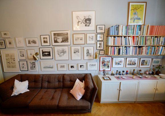 Ruskea sohva, jonka takana on seinällä pieniä tauluja. Vieressä on hyllyjä täynnä kirjoja.