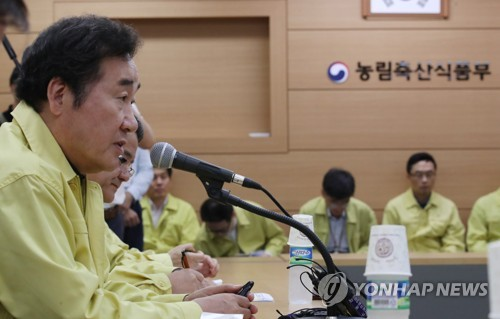 Prime Minister Lee Nak-yon (L) speaks at a meeting at the Ministry of Agriculture, Food and Rural Affairs in Sejong on Aug. 19, 2017, amid the tainted egg crisis. (Yonhap)