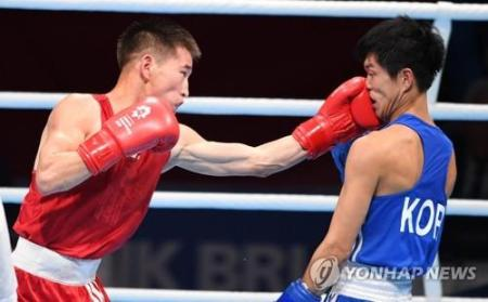 Asian Games  Defending boxing champ suffers defeat in qualifying round In this photo taken by the AFP  Enkhmandakh Kharkhuu of Mongolia  L  punches