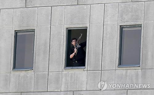 이란 의회 의사당 창문에 총을 든 남성이 서 있다[AP=연합뉴스자료사진]