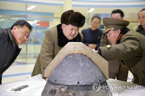 NK leader looks at suspected rocket warhead