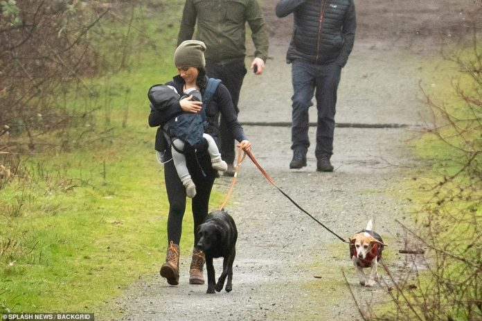 Megan Markle walks with her baby Archie and her dogs