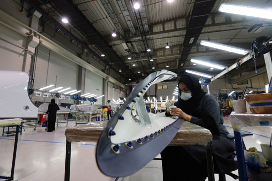 A woman working on a plane made in the factory
