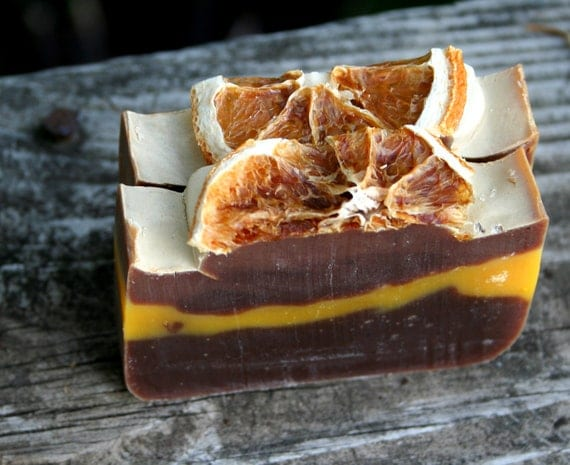 Two bars of soap that look like slices of chocolate orange cake: a half-orange slice on top of a white frosting-looking layer on top of an orange layer between two dark chocolate-colored layers.
