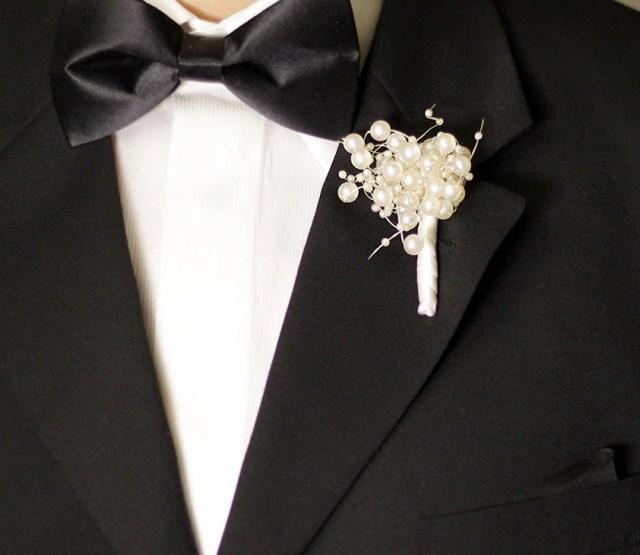 Boutonnière (flor de lapela para noivos) de pérolas.
