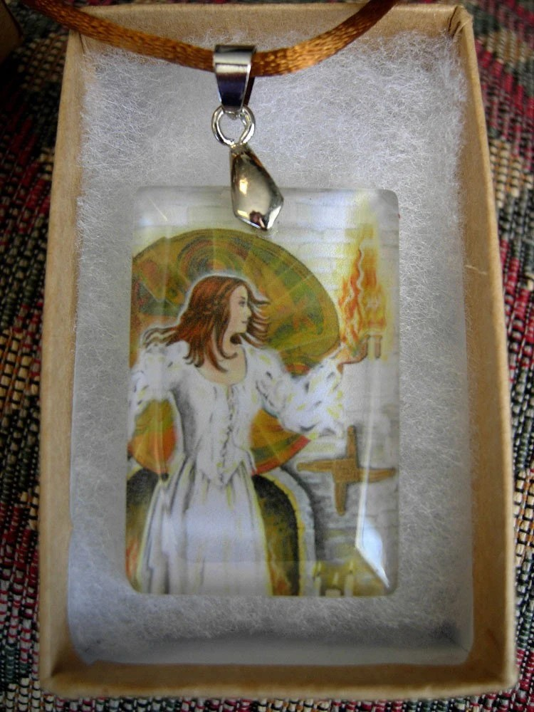 a pendant in a display box. the pendant shows a picture of the Goddess Brigid, with flame and distinctive cross, behind a crystal surface.