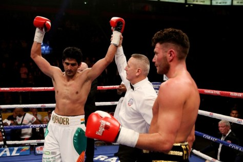 Vijender Singh made a smashing professional debut by knocking out Britain's Sonny Whiting in the middleweight category, ruthlessly demolishing the man, who promised to put him through hell at the Manchester Arena. Vijender won the contest with a few seconds left in the third of the four-round bout via Technical Knockout, pushing Whiting literally on to the ropes and smacking him with a combination of jabs and uppercuts before the referee stepped in to stop the contest. (Getty Images)