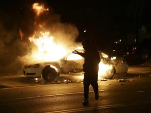 A man runs from a police car that is set on fire in Ferguson, Mo. The car Deandre Joshua was in was also set on fire.