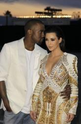 Kanye West whispers about his evil plans to Kim Kardashian at the Cannes Film Festival on May 23, 2012.