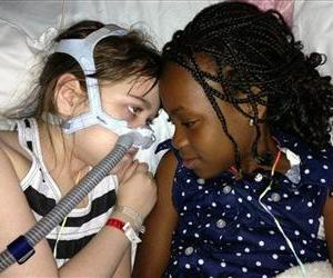 In this May 30, 2013 photo provided by the Murnaghans, Sarah Murnaghan, left, lies in her hospital bed next to adopted sister Ella on the 100th day of her stay in Children's Hospital of Philadelphia.
