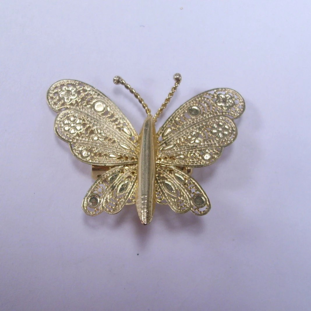 Gold toned filigree metal butterfly brooch
