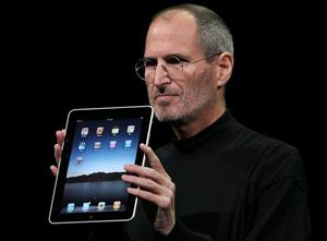 Apple CEO Steve Jobs holds up the new iPad.