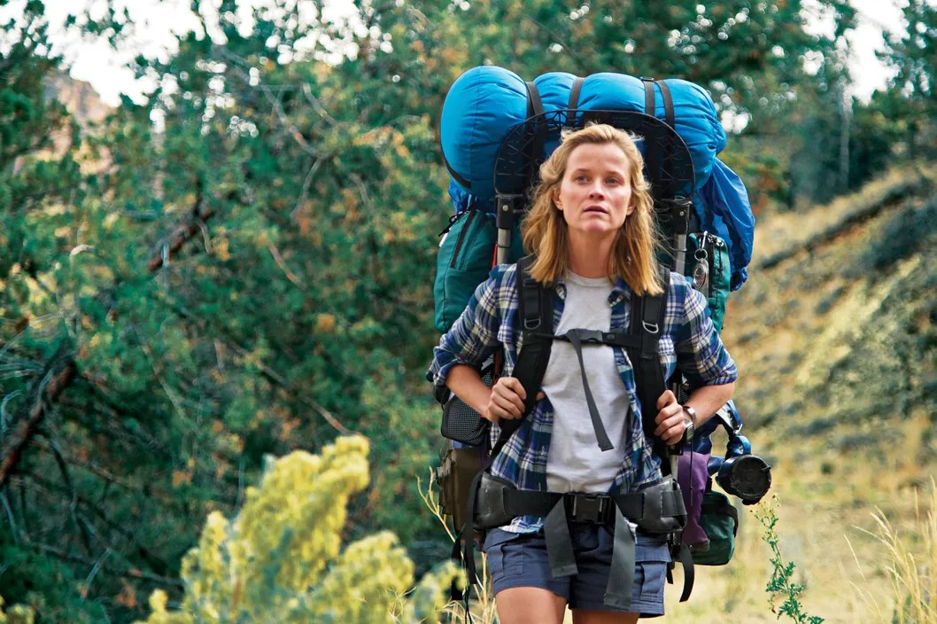 Reese Witherspoon in Wild (2014). Cheryl, a petite blonde woman in cargo shorts and a plaid shirt, carries an enormous hiking backpack on her shoulders. She is walking through a wooded area with green trees, gazing out in front of her.