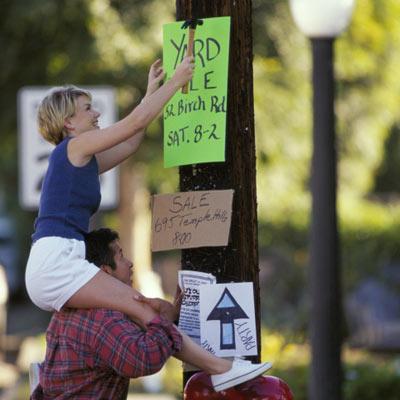 couple nailing up yard sale sign