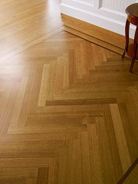 closeup of a herringbone floor, with part of the white baseboard and the leg of a chair off to the side
