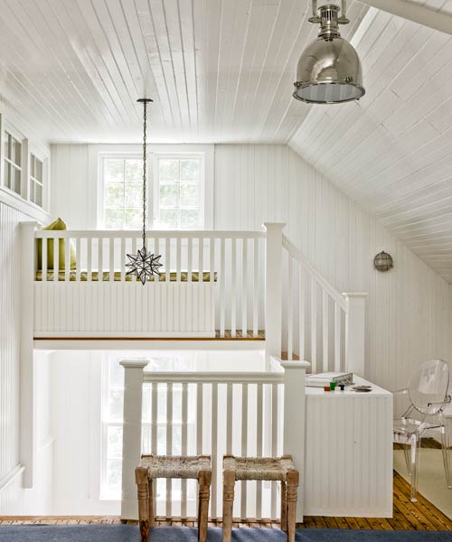 white multiple-level staircase wrapping it's way from floor to floor, with white railings, white beadboard walls, and white beadboard ceilings