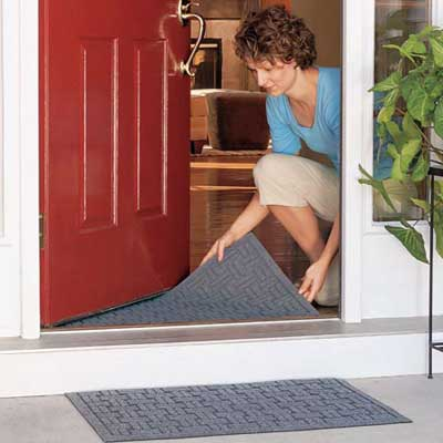 woman laying down door mats outside and inside an entryway